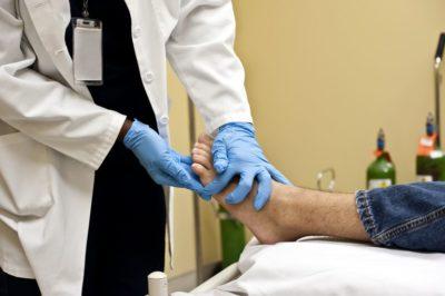 врач осматривает стопу