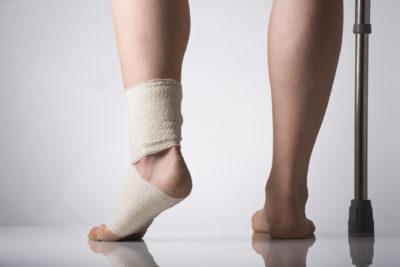 на костылях с перебинтованной ногой