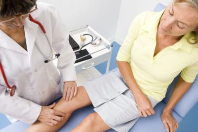 врач обследует колено