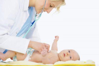 врач осматривает младенца