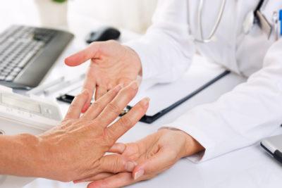врач осматривает кисти рук